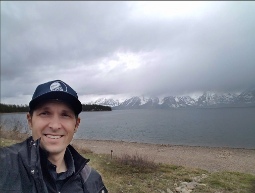Jason Czarnezki in front of lake and mountains